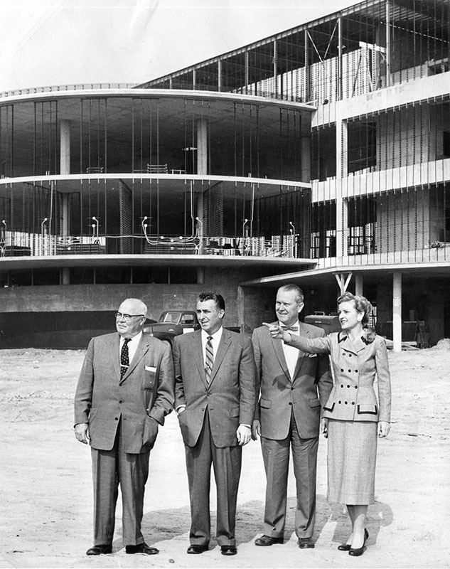 """March 18, 1957 reads """"Discussing modern innovations of Valley Presbyterian Hospital, nearing completion at 15107 Vanowen St., are Mrs. Barbara Holt, member of hospital's board of directors, and from left, J. H. Wray, Jim Cross and Walter Rueff, members of San Fernando Automobile Dealers Association committee for hospital's fund drive.""""  (LAPL)"""